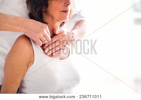 An Unrecognizable Physiotherapist Working With An Old Female Patient. Copy Space.