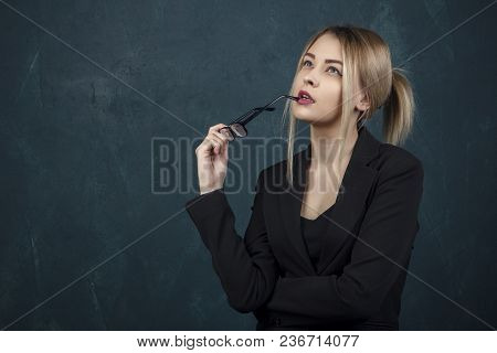 Portrait Of A Beautiful Woman In Glasses In A Black Suit Against A Blue Textural Wall With Space For