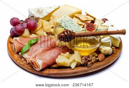 Camembert Cheese And Prosciutto With Honey, Figs, Walnuts On Wooden Cutting Board