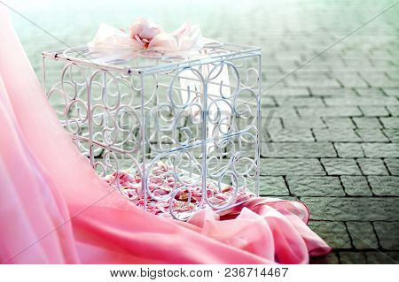 Pink Flowers In A Cage, On A Cobblestone With A Pink Tablecloth. Wedding, Gift, Decoration, Baby Sho