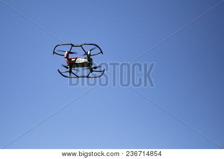 A Flying Drone, Hovering In A Blue Sky