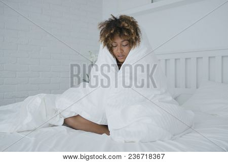 Young curly ethnic model sitting on bed in morning and wrapping in warm blanket looking unhappy with cold temperature.