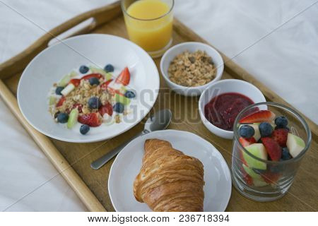 From above view oh delicious fruit mix served with juice and croissant on wooden tray above white blanket of bed.