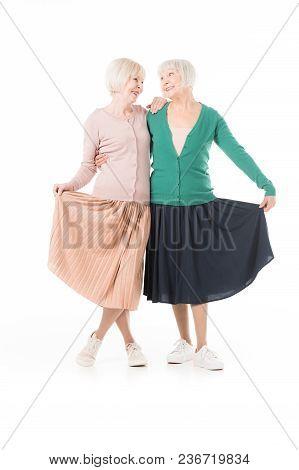 Smiling Stylish Senior Women Holding Skirts Isolated On White