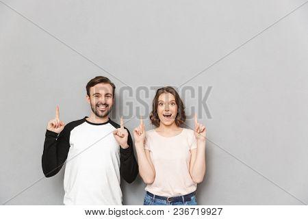Image of cheerful emotional couple friends standing isolated over grey wall background looking camera pointing.