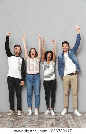 Image of emotional excited group of friends standing isolated over grey wall background looking camera pointing.
