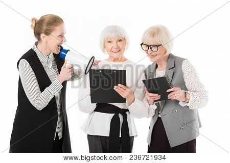 Mature Businesswoman With Megaphone And Two Senior Businesswomen With Clipboard And Textbook Isolate