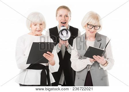 Mature businesswoman with megaphone between two senior businesswomen with clipboard and textbook isolated on white poster