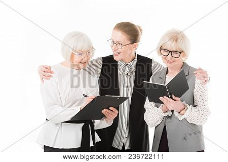 Two Senior Stylish Businesswomen Writing In Clipboard And Textbook While Mature Businesswoman Holdin