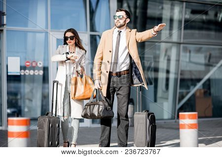 Business Couple Catching A Taxi Standing With Luggage Near The Airport