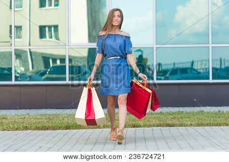 Happiness, Consumerism, Sale And People Concept - Smiling Young Woman With Shopping Bags.