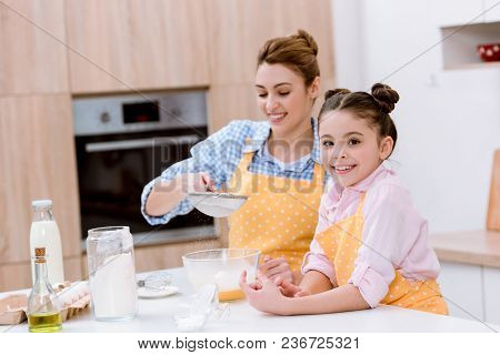 Happy Mother And Daughter With Sieve Preparing Dough For Pastry Together