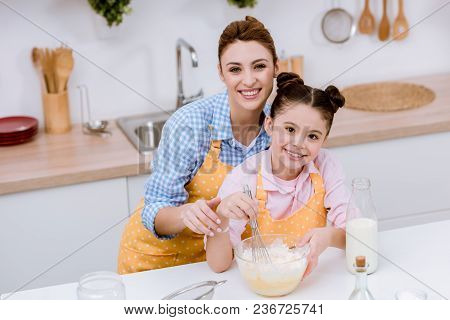 Mother And Daughter Mixing Dough For Pastry At Kitchen