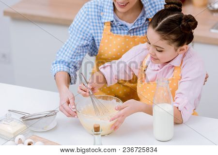 Cropped Shot Of Mother And Daughter Mixing Dough For Pastry