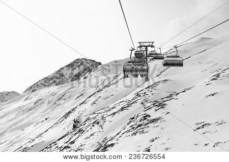 Cable Car At A Ski Resort. Chairlift With Skiers. Mountains Covered With Snow And Cloudy Day. Black