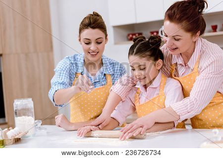 Three Generations Of Beautiful Women Rolling Dough For Cookies Together At Kitchen