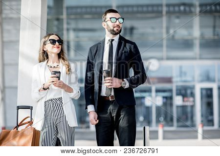 Business Couple In Suits Standing Near The Airport With Luggage During The Business Trip