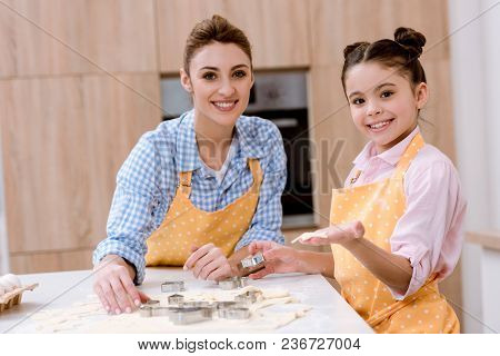 Mother And Daughter Cutting Dough For Cookies Together At Kitchen