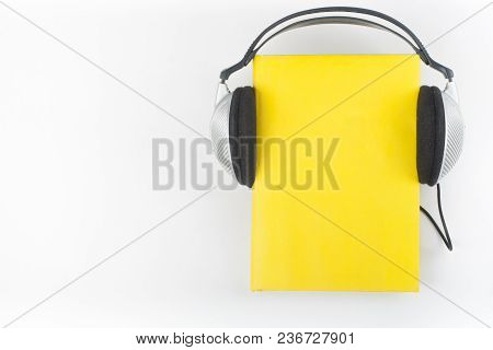 Audiobook On White Background. Headphones Put Over Yellow Hardback Book, Empty Cover, Copy Space For