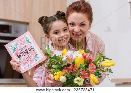 Embracing Mother And Daughter With Mothers Day Greeting Card And Bouquet