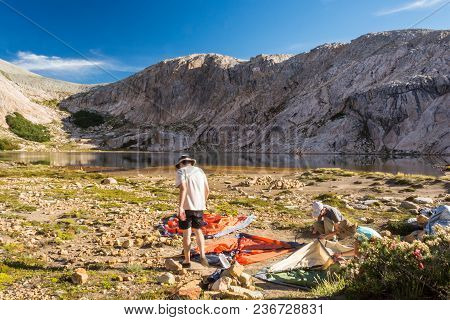People, Men And A Woman, Making A Camping Tent At A Remote Campsite In The Wilderness Of The Mountai