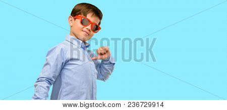 Handsome toddler child with green eyes proud, excited and arrogant, pointing with victory face over blue background
