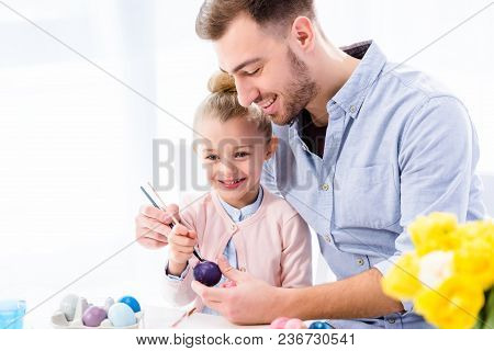 Father Helping Daughter To Color Easter Eggs