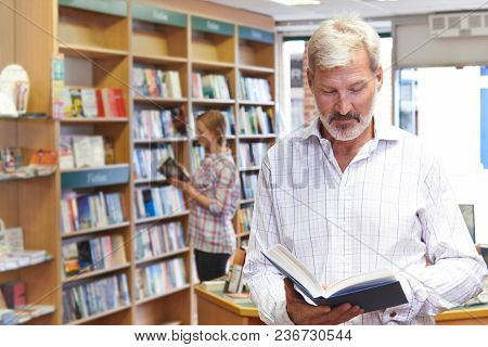 Male And Female Customers Browsing Books In Bookshop