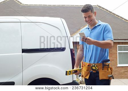 Builder With Van Checking Text Messages On Mobile Phone Outside House