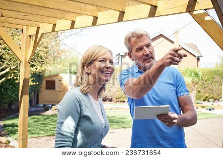 Mature Woman Discussing Plan With Landscape Gardener Using Digital Tablet