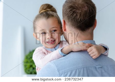 View Of Cute Preadolescent Daughter Embracing Father