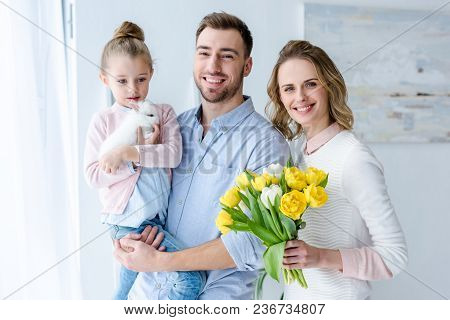 Happy Family Embracing And Holding Bunny And Tulips
