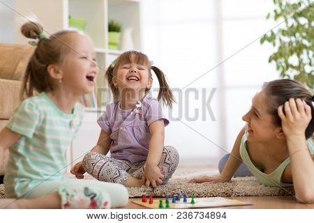Mother And Her Kids Daughters Playing In Board Game