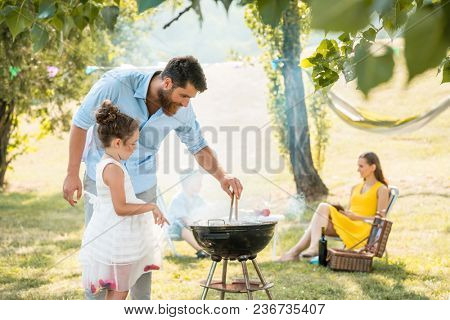 Side view of a cute girl watching her father preparing meat on a round charcoal barbecue grill outdoors during family picnic in a summer day