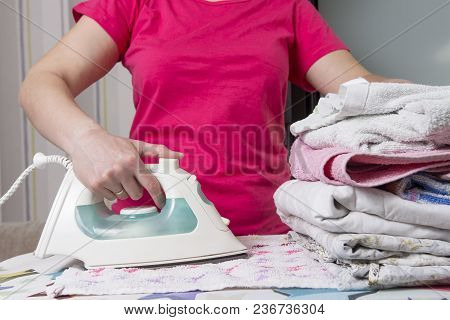 servant strokes washed laundry with iron on ironing board. Housewife with iron at home ironing clothes poster