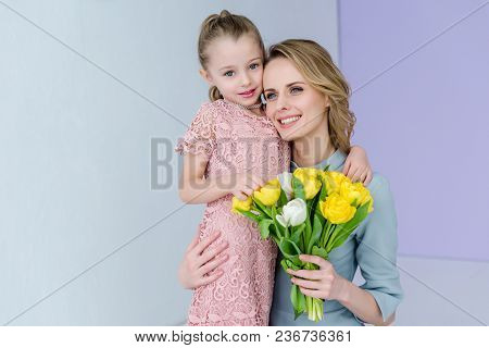 Woman Holding Bouquet And Embracing Cute Daughter On Women's Day