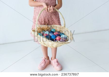 Child Holding Basket With Colored Easter Eggs