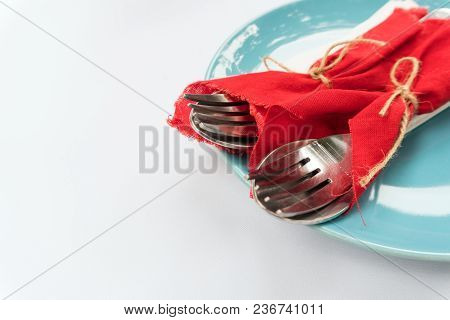 Two Pairs Of Spoon And Fork Tied With The Red Clothes, Placed On Blue Round Plate