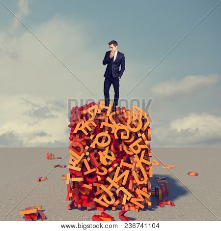 thinking businessman standing on letters tower