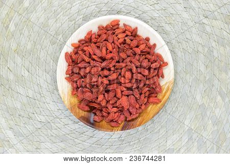 Heap Of Dried Goji Berries Placed In Eco Natural Banana Leaf Plate On Bamboo Mat Background Surface