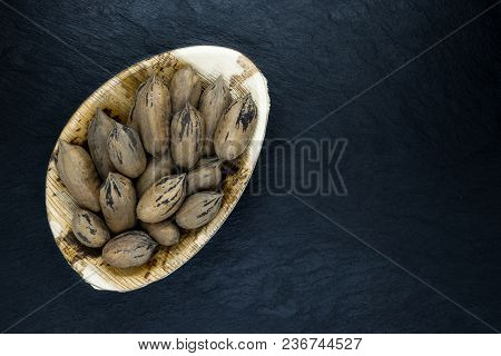 Pecan Nuts With The Nutshell In Eco Natural Banana Leaf Plate On Black Stone Background Surface With