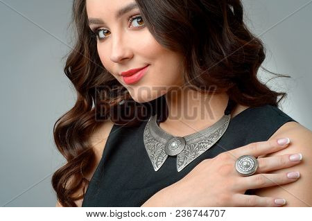 Beautiful Model, Curls, Bright Makeup, Jewelry And Red Lips. The Beauty Face. Portrait Shot In The S