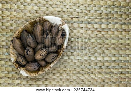 Pecan Nuts With The Nutshell In Eco Natural Banana Leaf Plate On Natural Bamboo Mat Surface With Fre