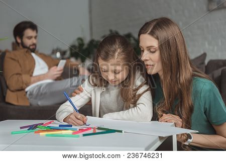 Mother Helping Daughter Drawing With Felt-tip Pens In Living Room