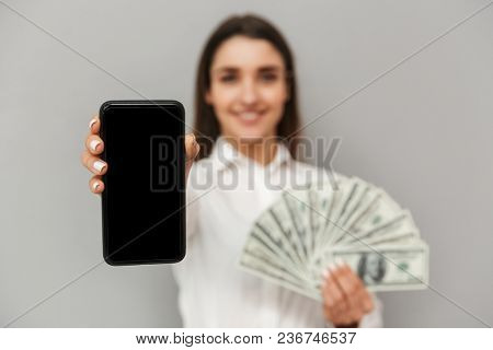 Lucky woman 20s in black and white wear smiling and demonstrating black copyspace screen of cell phone at camera with lots of money in hand isolated over gray background