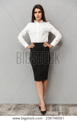 Full length portrait of caucasian woman with long brown hair in business wear keeping arm on waist and frowning with strict gaze isolated over gray background