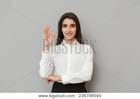 Portrait of beautiful woman with long brown hair in business wear smiling and showing ok sign isolated over gray background