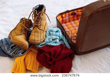 Woman Clothes Near Old Vintage Suitcase. Travel Concept. Preparing For Winter Trip