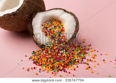 Ripe Coconut Halves With Colorful Candy Sprinkles Inside On Pink Studio Backdrop. Creative Backgroun