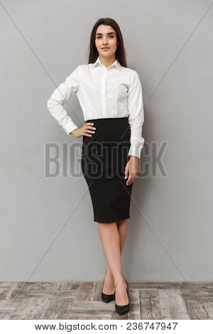 Full length portrait of caucasian woman with long brown hair in business wear smiling at camera and keeping arm on waist isolated over gray background